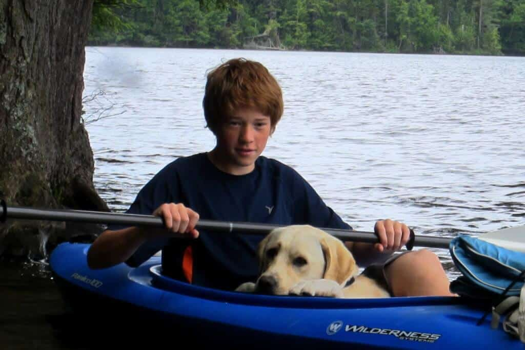 Rowan and a yellow labrador sitting in a kayak in the Adirondacks