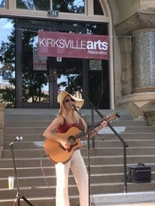 A woman plays a guitar at the summer concert series in Kirksville, Missouri