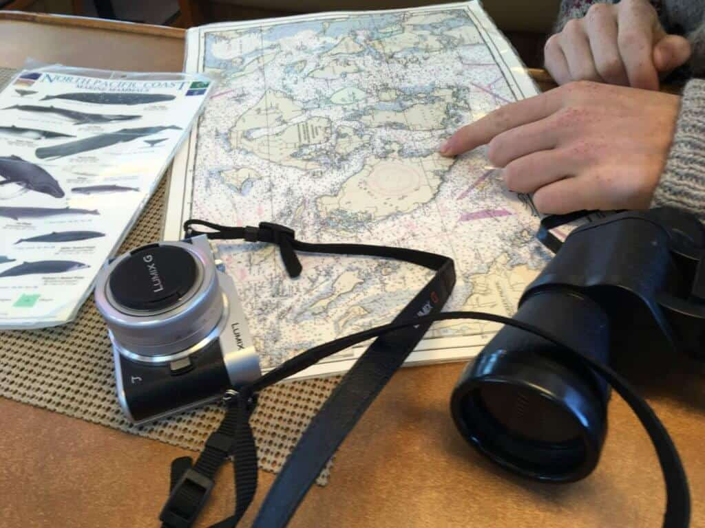 a map of the Puget Sound, binoculars, and a camera