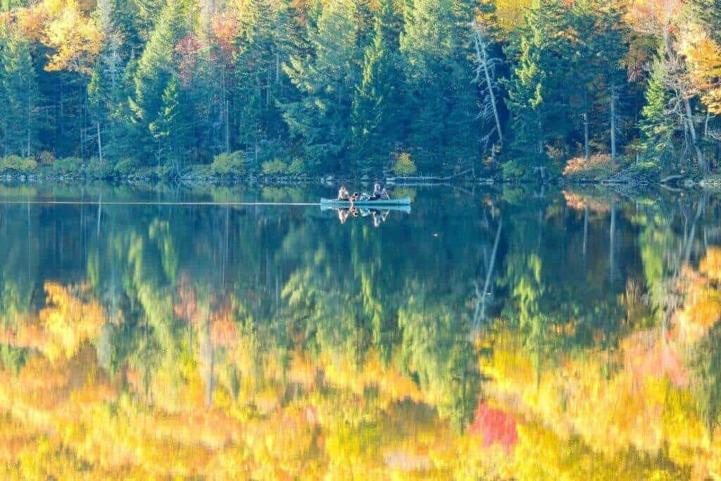 Fall reflections in Grout Pond, VT with a single blue canoe paddling across the water.