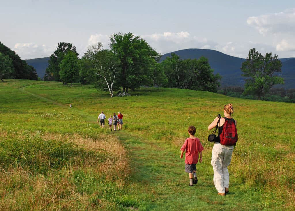 A family hikes through the meadow at the Clark Art Institute in Willamstown, MA
