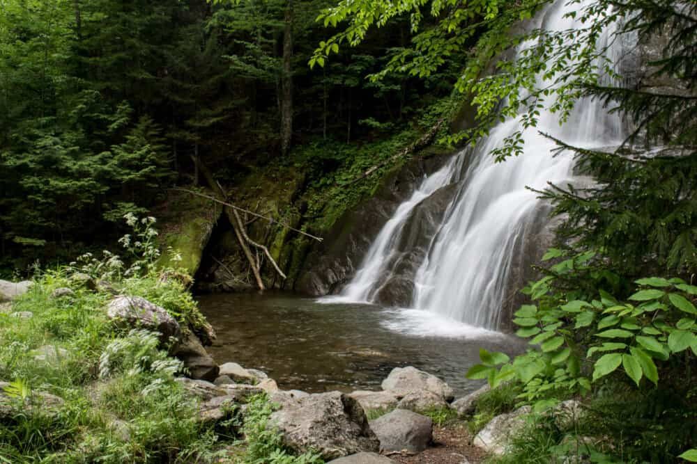 Moss Glen Falls in Granville, Vermont, surrounded by green foliage.