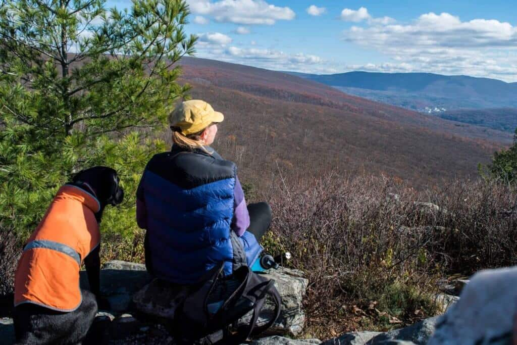 A woman sits next to a black dog at the top of Pine Cobble Mountain in Williamstown, Massachusetts.