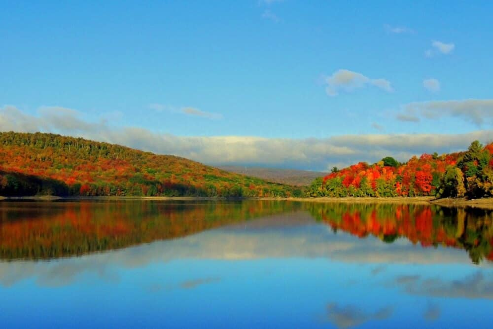 Ward's Cove in Wilmington, VT. A view of blue skies, colorful fall foliage in the mountains, and clear blue water.