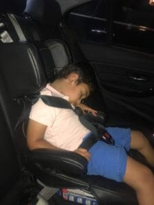 A young boy sleeps soundly in a car seat.