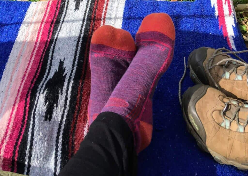 A pair of pink and purple Darn Tough Vermont sicks on a colorful blanket
