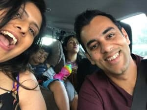 A selfie of several people in a car driving on a long road trip