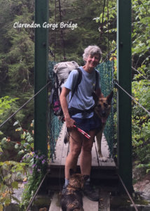 A woman stands on the Clarendon Gorge bridge. she is wearing a backpack and standing next to a German Shepherd.