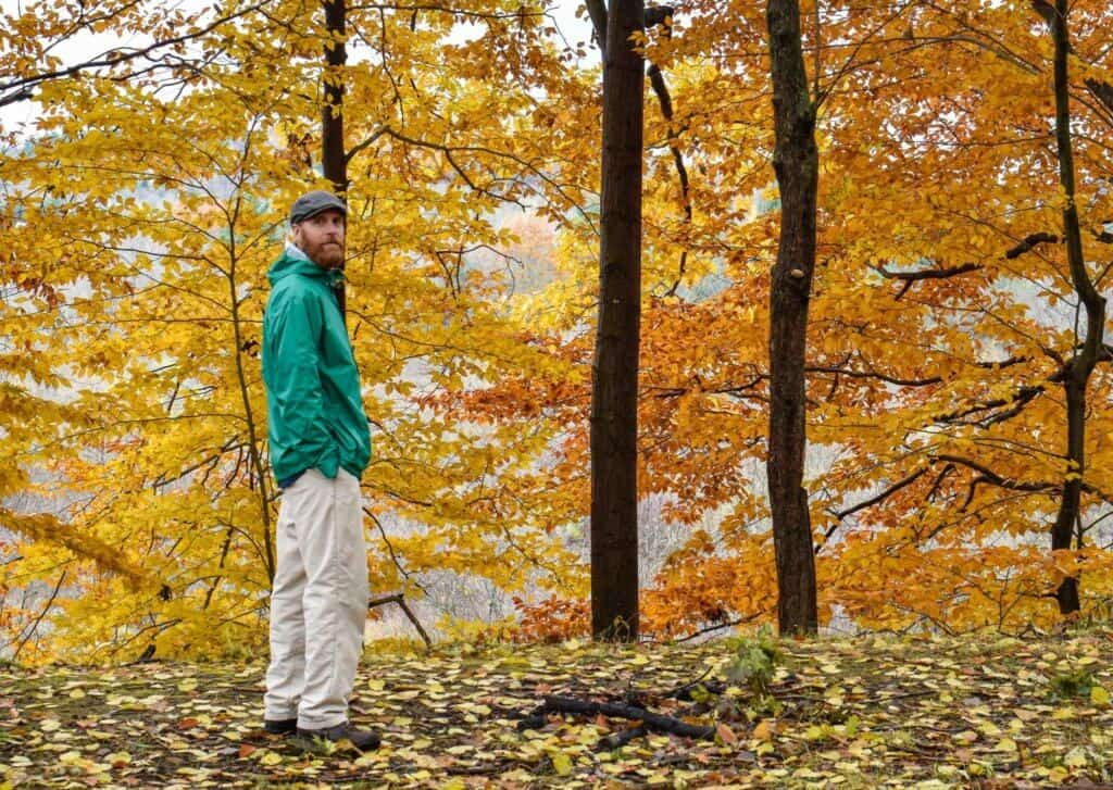 a man stands in a forest full of colorful fall foliage.