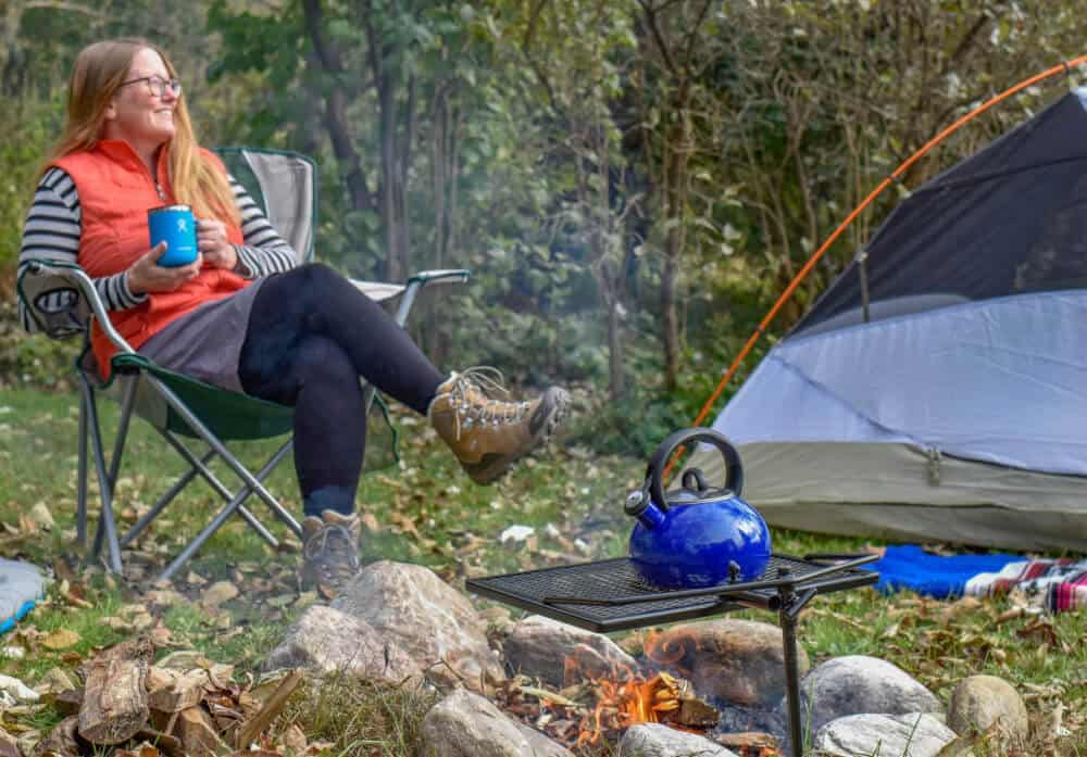 A woman sits near a camp fire holding a cup of steaming tea.