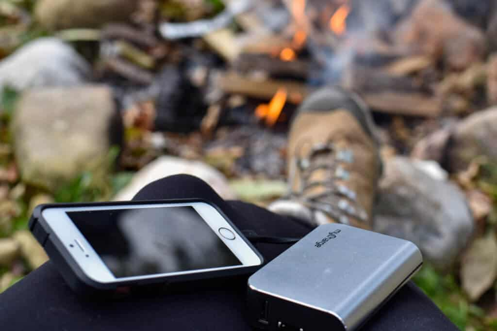 Travel photography gear - A cell phone connected to a portable charger, near a campfire