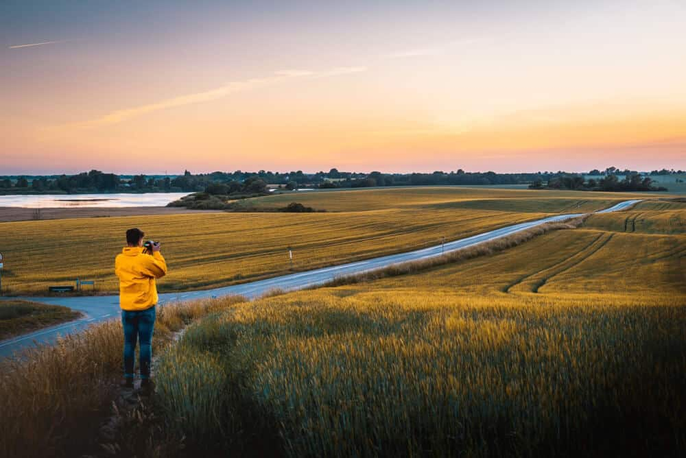 A man stands in a field near a stream photographing the sunset.