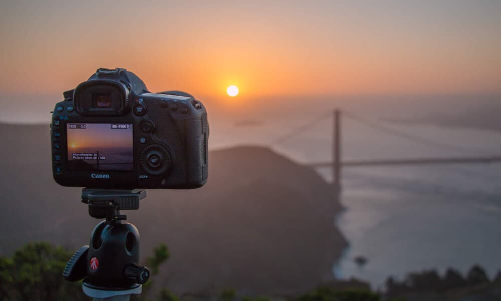 travel photography gear - a camera photographs the Golden Gate Bridge at sunset.