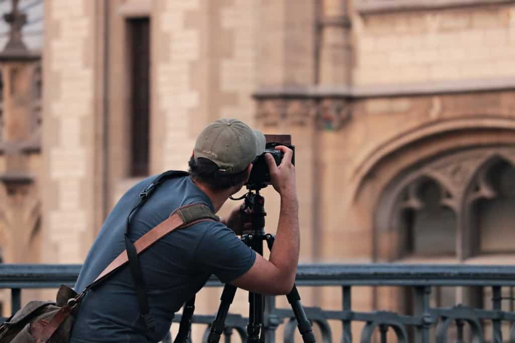 A man is shown from the back looking through a camera toward some buildings.