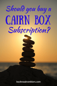 A silhouette of stacked rocks in the sunset. Caption reads: Should you buy a Cairn box subscription?