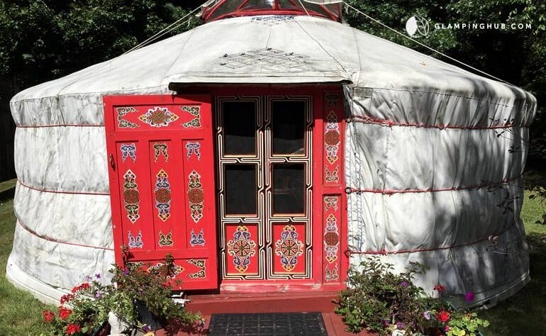 A white yurt with a red door in Saratoga Springs, NY
