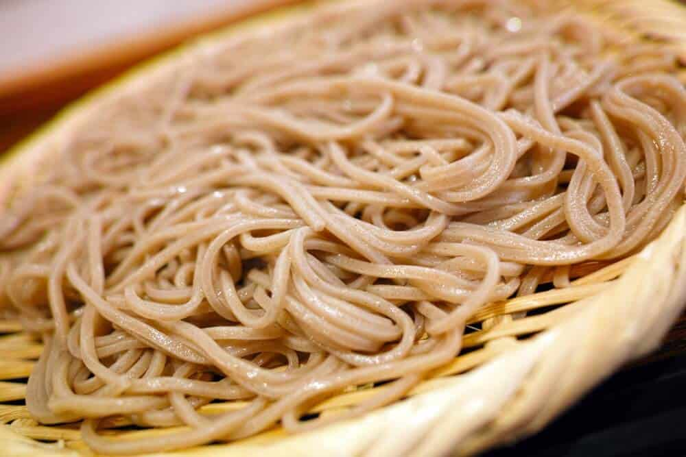a close-up of peanut noodles with spicy peanut sauce