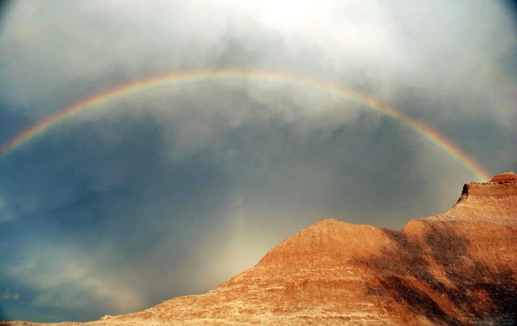 A rainbow in a cloudy sky over Badlands National Park