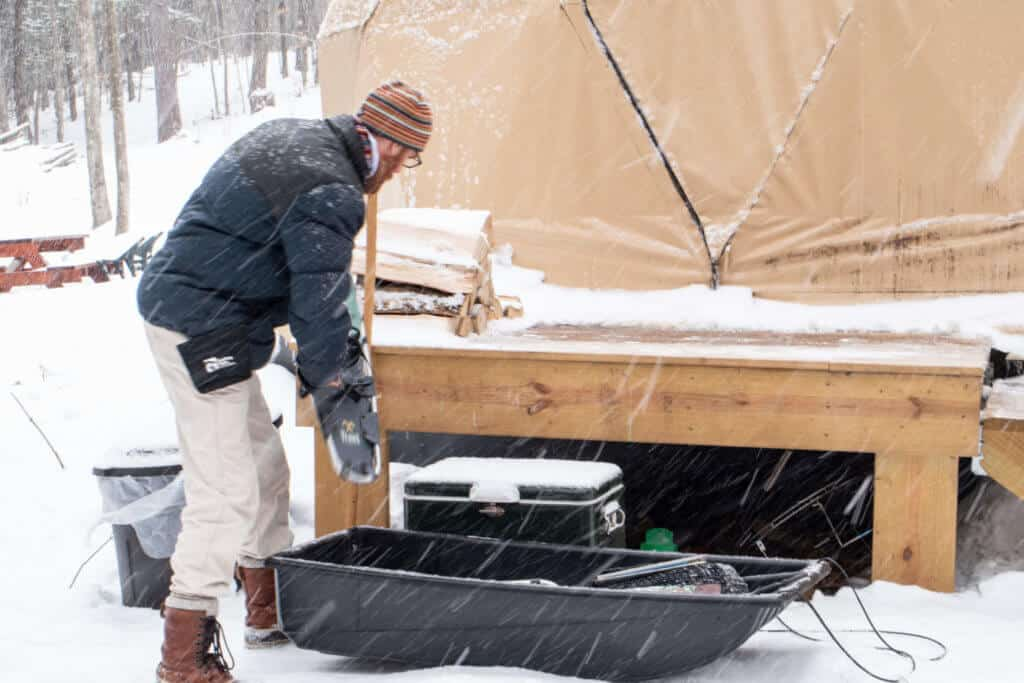 A man unloading a utility sled next to a camping shelter in Vermont.