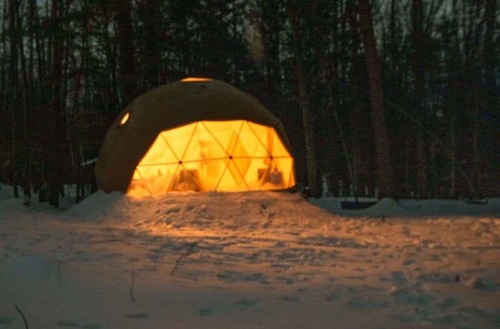 A geodesic dome lit from the inside at night. Putney, Vermont