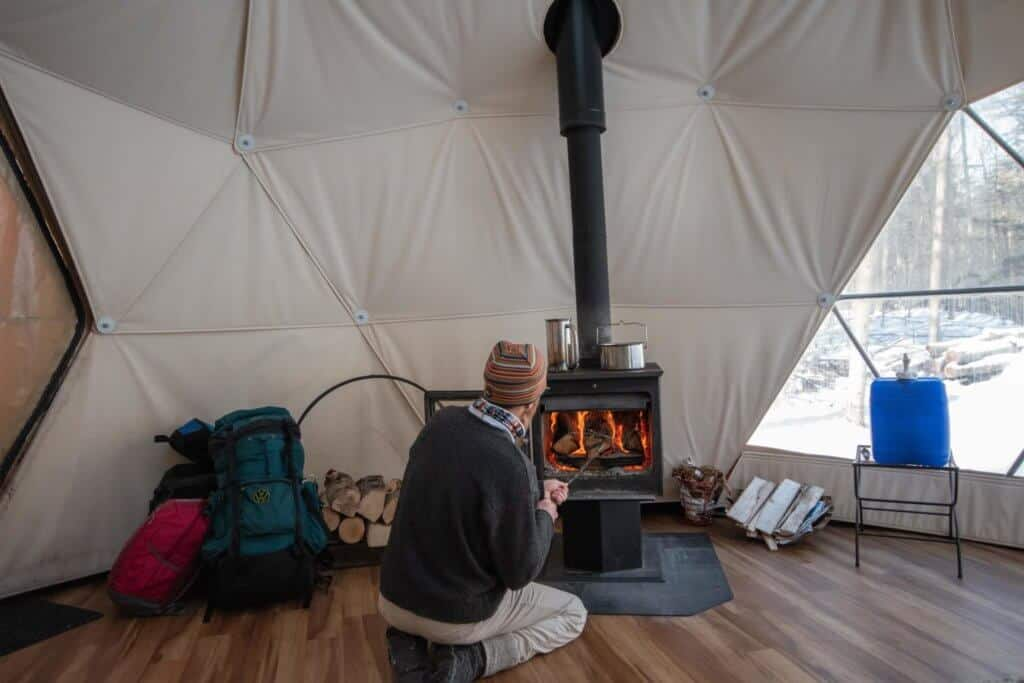 A man kneels down in front of a woodstove inside a geodesic dome in Putney, Vermont.