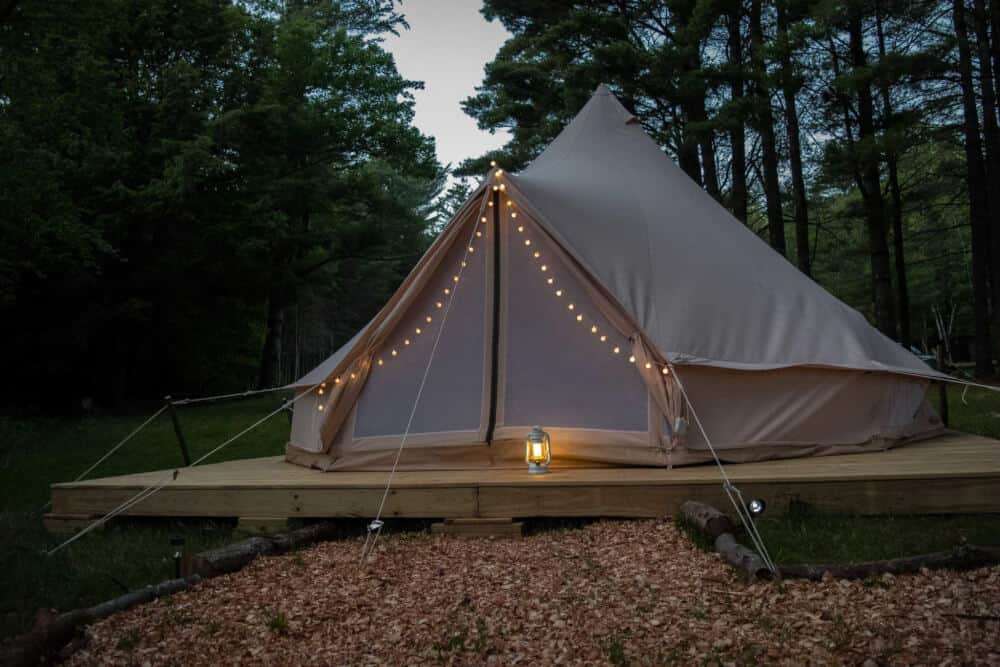 A glamping tent in the evening with fairy lights.