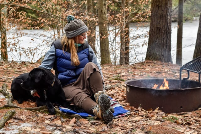 A woman sits near a campfire with a black Labrador.