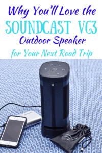 The Soundcast VG3 outdoor speaker next to an iPhone and a portable power bank. Caption reads Why you'll love the Soundcast VG3 Outdoor Speaker for your next Road Trip.
