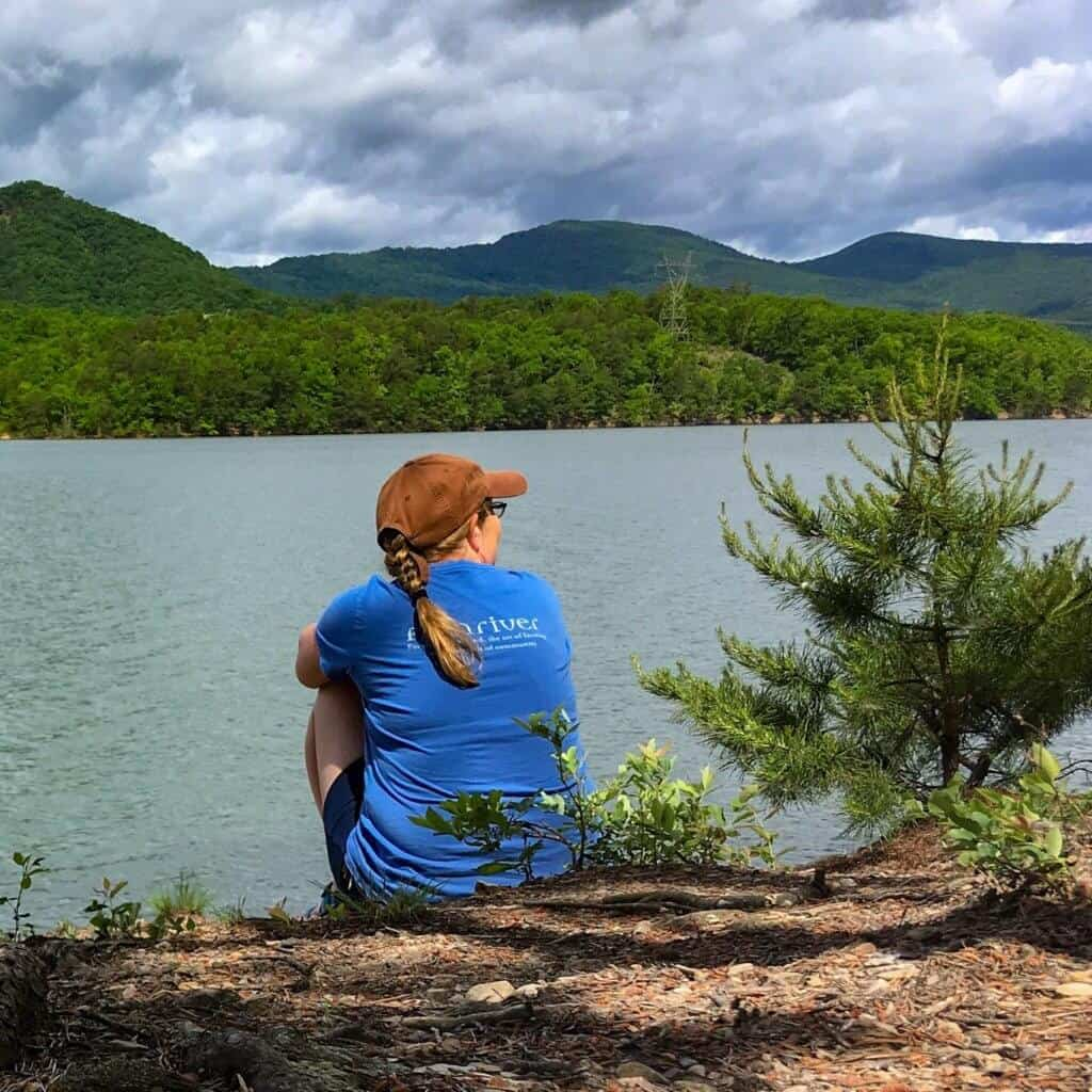 A woman sits by the shore of Carvins Cove Reservoir in Roanoke, Virginia.