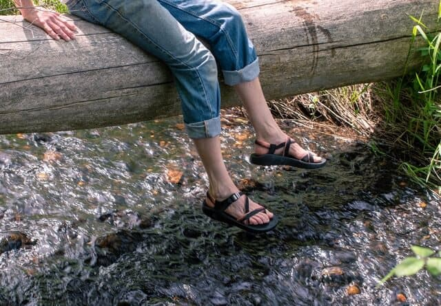 dangling feet above a stream. The feet are wearing Chaco sandals.
