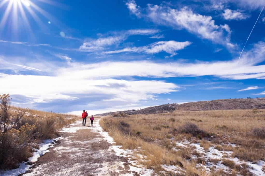 Two people walk on a winter trail in Coyote Ridge Natural Area in Fort Collins, Colorado.
