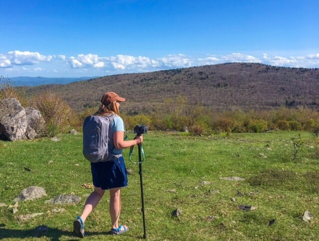 A woman hikes in the mountains of Virginia with a hydration pack and a camera.