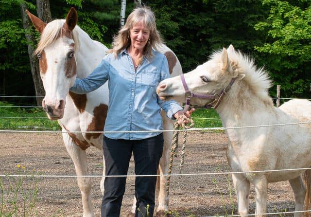 Ellen stands with horses, Maya and Nahvee