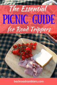 A cutting board with cheese, meat, and tomatoes. Caption reads: The Essential Picnic Guide for Road Trippers