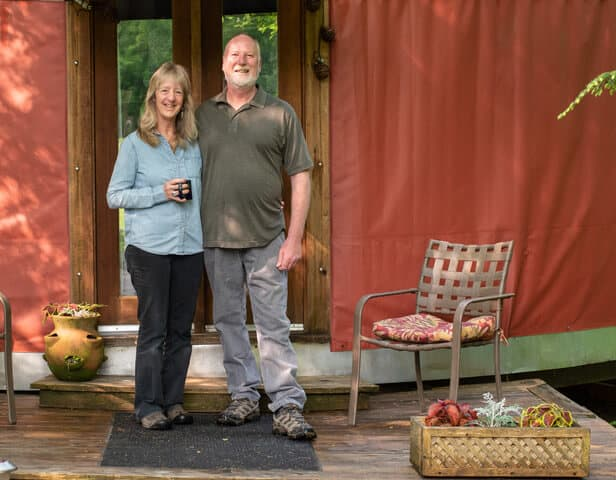 hosts Ellen and Jay standing in front of their yurt rental.