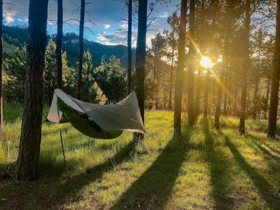 The Kammok Mantis camping hammock swings from two trees in the sunset.