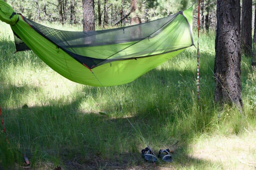 An empty hammock with a pair of sandals beneath it.
