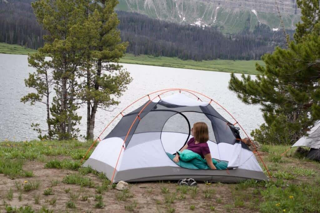 a woman lies in a tent next to a lake in Wyoming.