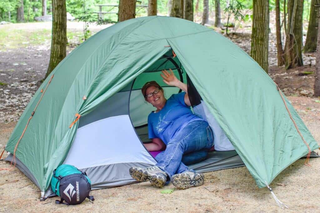 A woman lies inside of a tent smiling at the camera.
