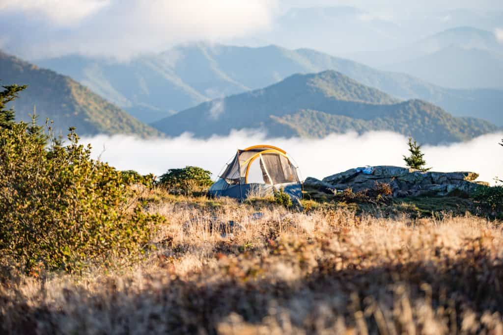 a tent in a field surrounded by mountains and fog.