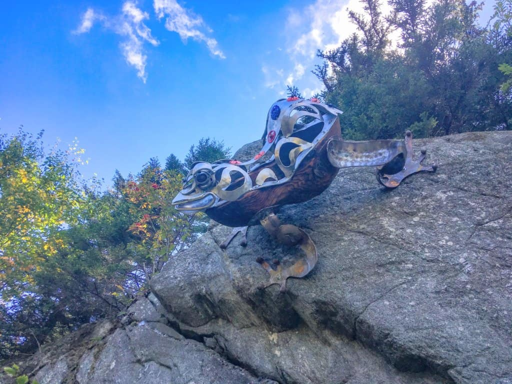 A giant metal and wood sculpture of a tree frog, perched on a boulder at Mont Sutton in Quebec.