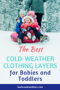 Three kids on a sled on a snowy hill. caption reads: The best cold-weather clothing for babies and toddlers.