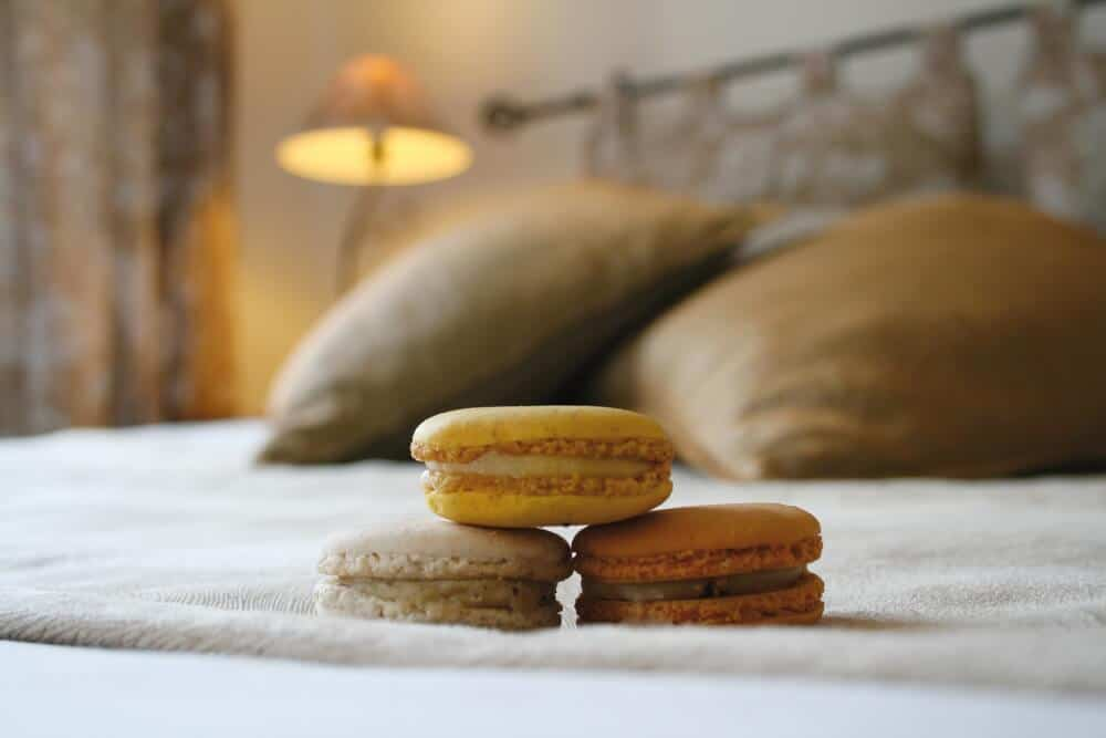 A close-up of macrons stacked on a bed at a small boutique hotel.