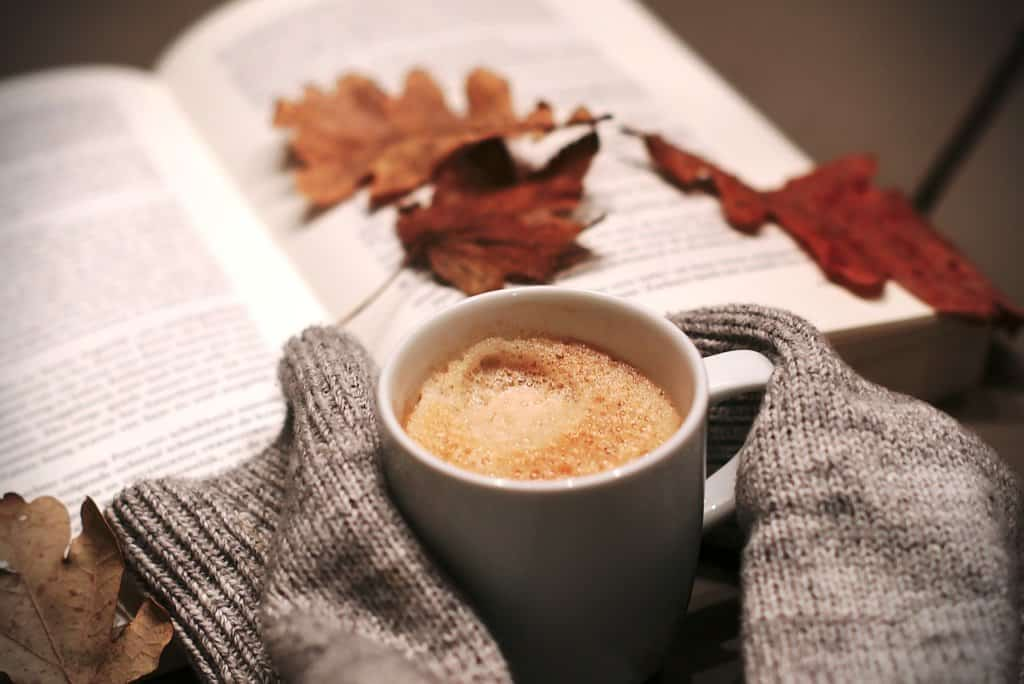 An open book with fall leaves, a coffee cup, and the sleeves of a wool sweater.