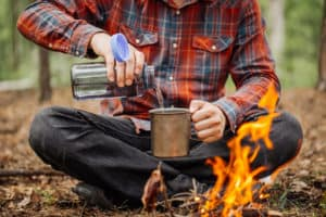A man pours water into a camping mug.