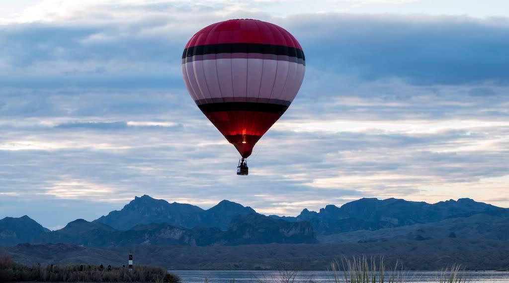 A single hot air balloon floats over the mountains in Lake Havasu City, AZ