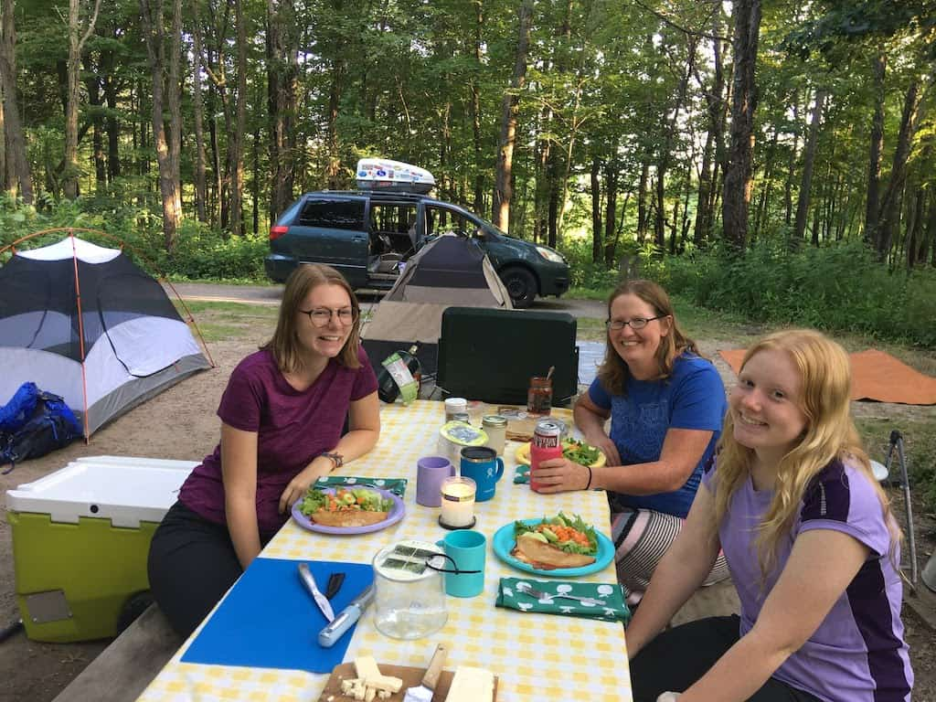 Three women sitting at a picnic table at Dunewood Campground in Indiana Dunes National Park.