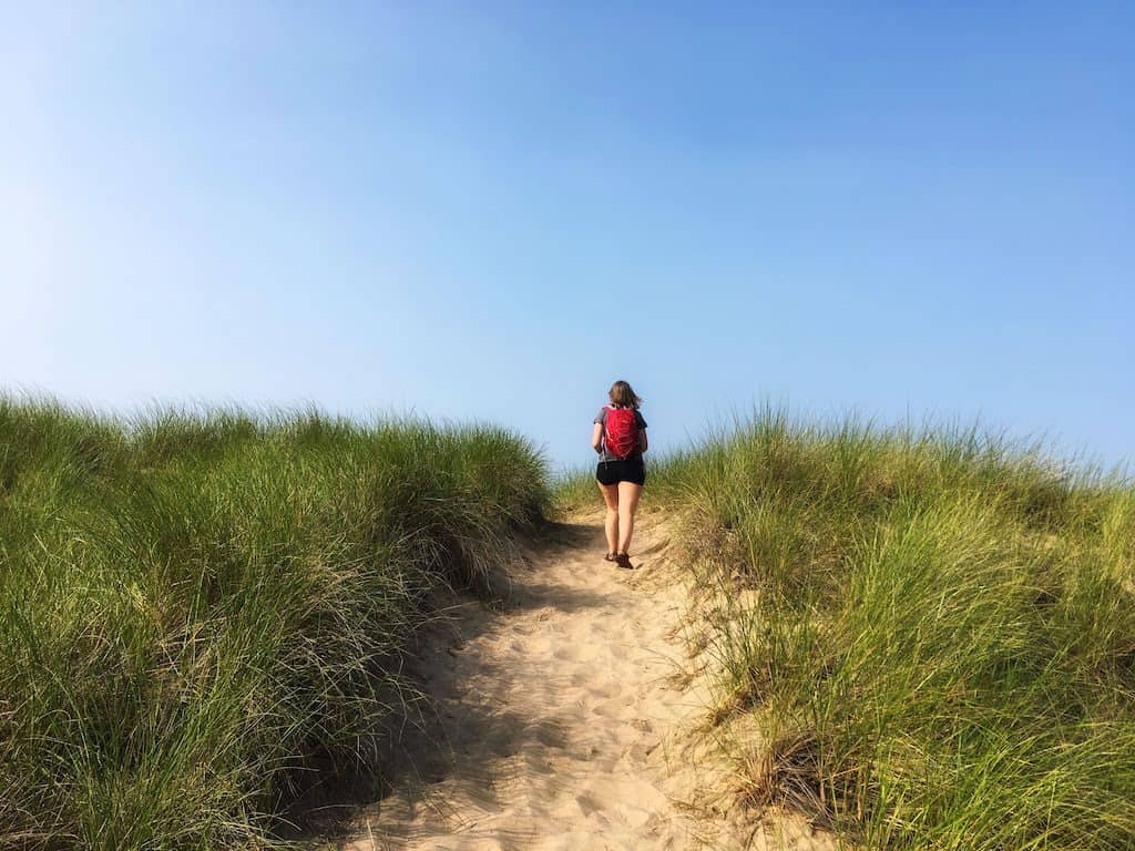 A woman hikes up and over a sand dune in Indiana Dunes National Lakeshore.