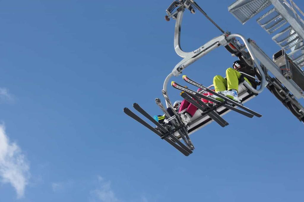A worms eye view of a ski lift with several skiers riding.