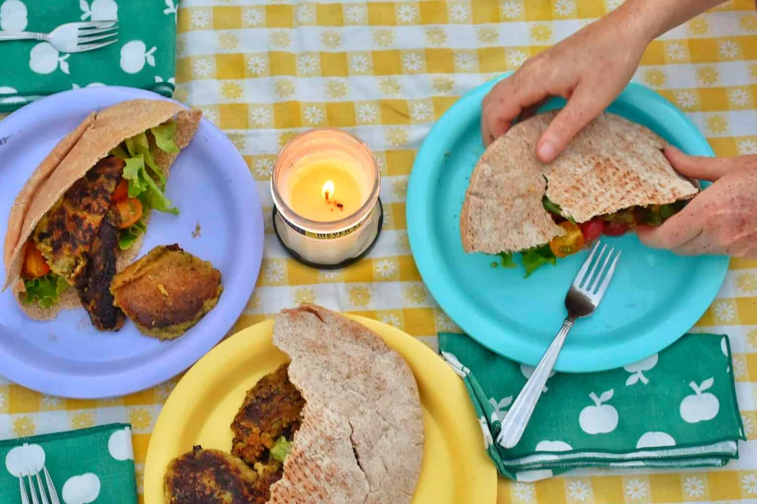 A close up of some camping food on a yellow checked tablecloth.